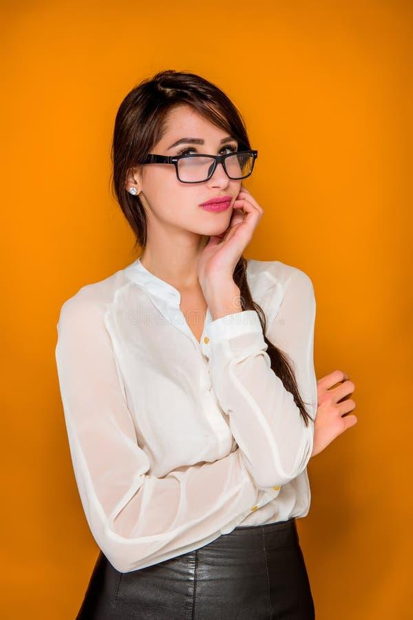 La jeune belle femme frustrante sérieuse d'affaires sur le fond orange photos libres de droits