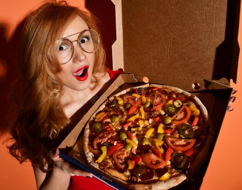 La jeune belle femme mangent de la pizza entière végétarienne mexicaine dans la boîte sur l'orange photos stock