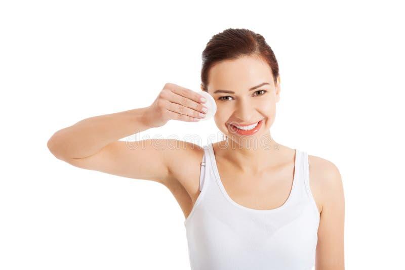 La jeune belle femme nettoie le maquillage d'oeil photo libre de droits