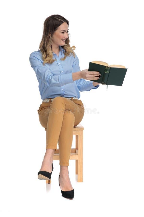La jeune belle femme repose et montre à quelqu'un quelque chose dans son livre photographie stock libre de droits