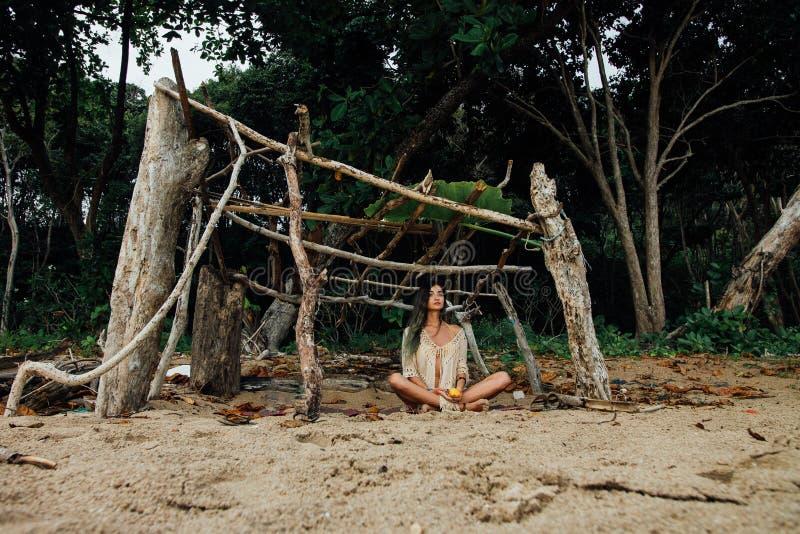 La jeune belle femme s'assied en position de lotus dessus sur la forêt tropicale de fond photo libre de droits
