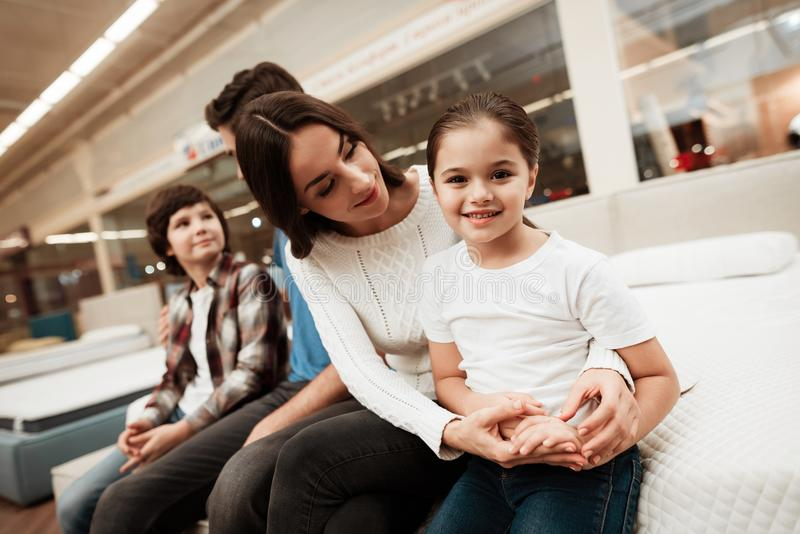 La jeune belle femme s'assied sur le matelas orthopédique avec le garçon et la fille gais dans le magasin de meubles photos libres de droits