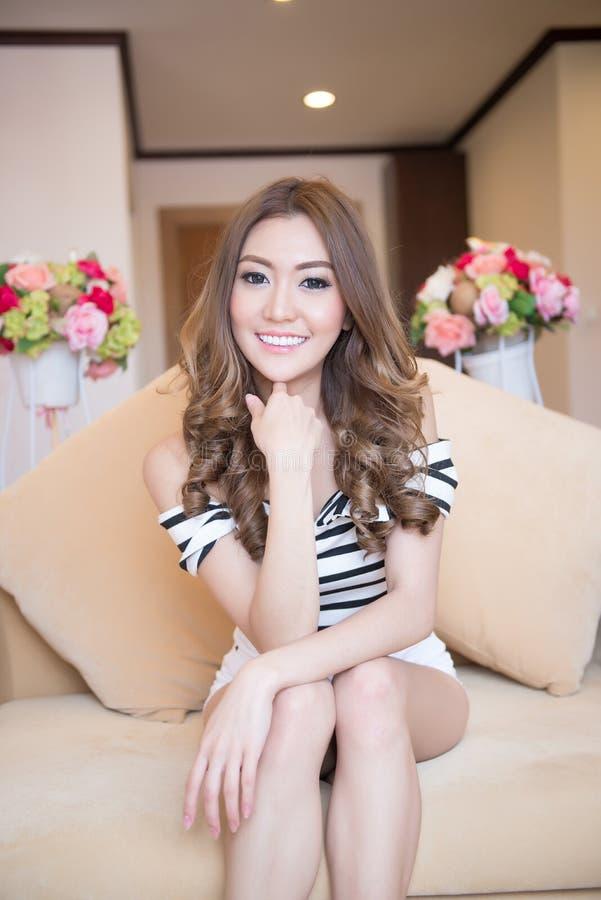 La jeune belle femme s'assied sur le sofa heureusement image stock