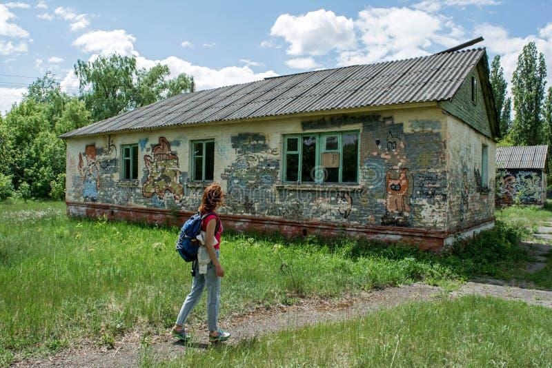 La jeune belle femme s'est perdue dans la colonie de vacances abandonnée photographie stock libre de droits