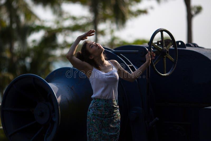 La jeune belle femme se tient sur le moteur géant d'un bateau abandonné photos libres de droits