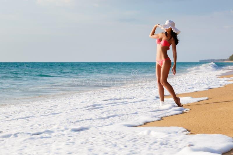 La jeune belle femme sexy dans un maillot de bain et un chapeau sur a image stock