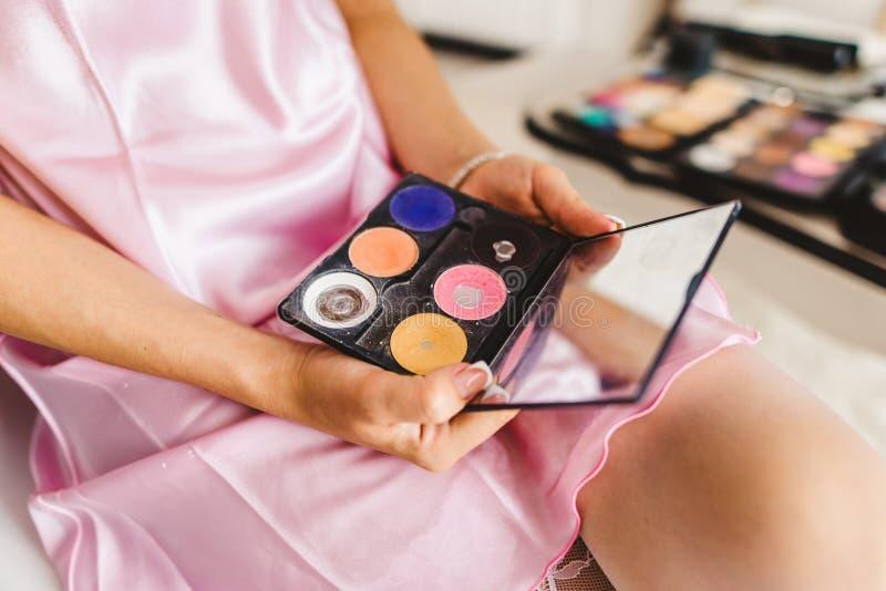 La jeune belle femme tient des ombres avec le miroir pour le maquillage photo libre de droits
