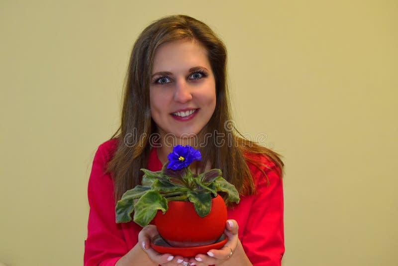 La jeune belle femme tient une violette images stock