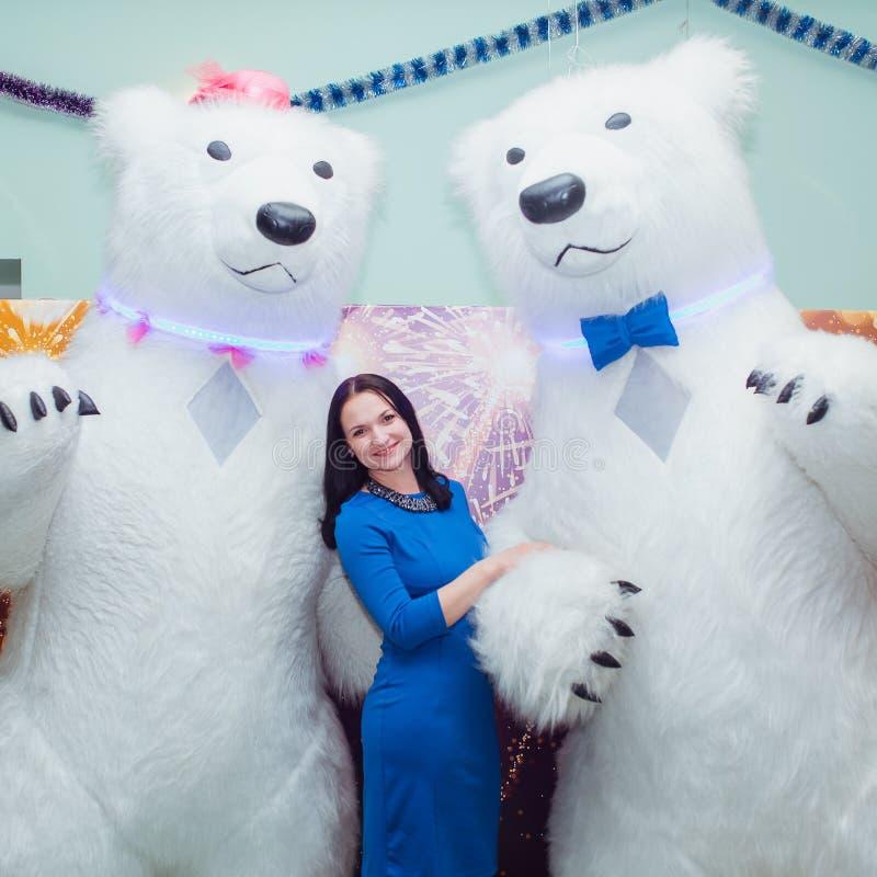 La jeune belle fille à la partie est photographiée avec les grands ours photo libre de droits