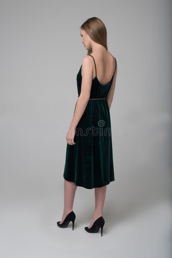 La jeune belle fille aux cheveux longs marche loin dans la robe vert-foncé images libres de droits