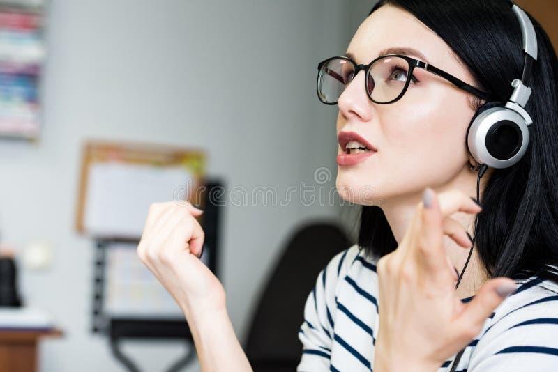 La jeune belle fille avec des écouteurs apprend la langue photo stock
