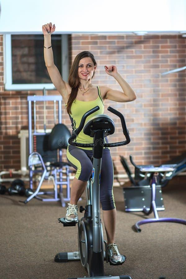 La jeune belle fille blanche dans un costume jaune et gris de sports est engagée sur un vélo stationnaire dans le centre de fitne image libre de droits