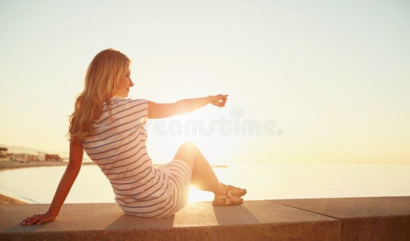 La jeune belle fille blonde s'assied sur la plage et apprécie le sunr photo stock