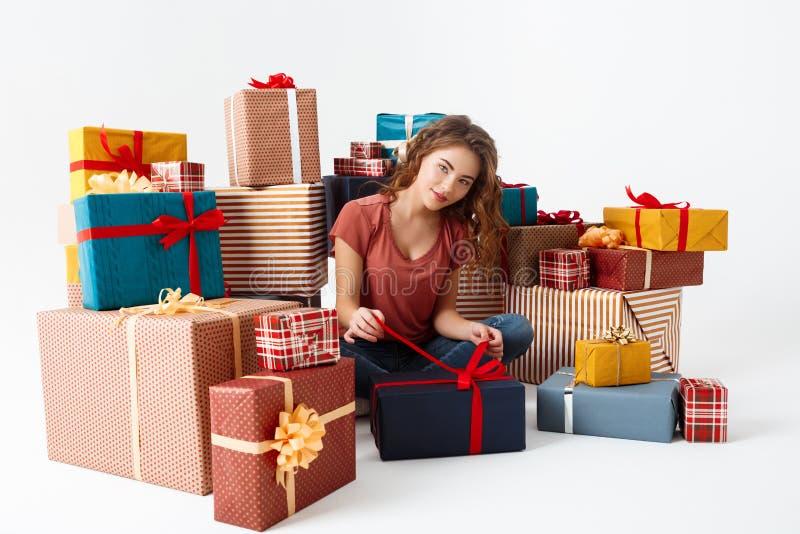 La jeune belle fille bouclée s'asseyant sur le plancher parmi des boîte-cadeau ouvrant l'un d'entre eux a isolé photo stock