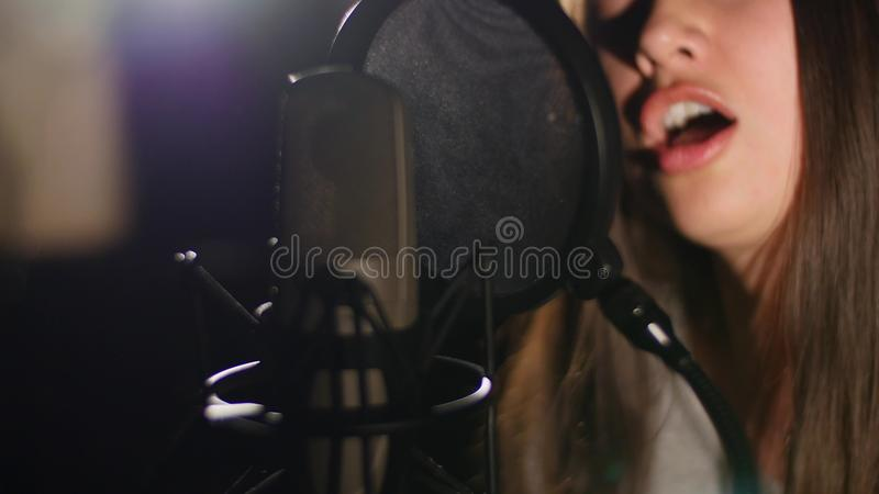 La jeune belle fille chante Jeune chanteur chantant dans un microphone Portrait étroit du chanteur image libre de droits