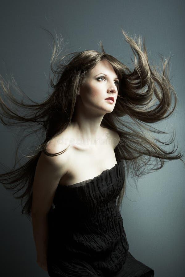 La jeune belle fille dans la robe noire photo stock