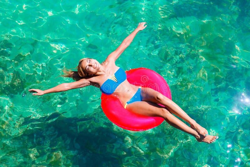 La jeune belle fille dans le bikini nage en mer tropicale sur un rubb photographie stock
