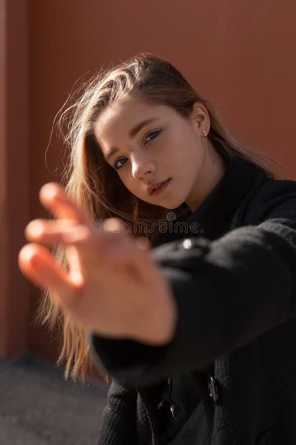 La jeune belle fille dans le manteau noir le jour ensoleillé étire sa main en avant Distribuez du foyer Essai de toucher la camér photographie stock