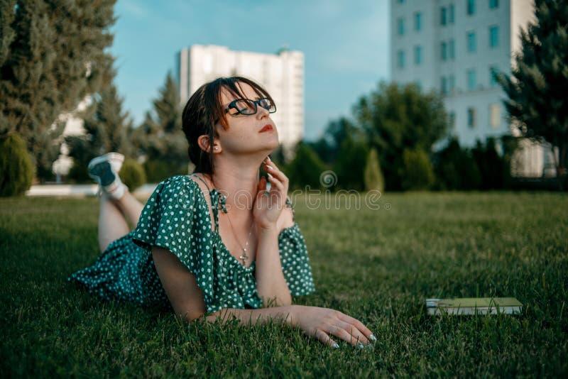 La jeune belle fille dans la robe de short d'été lit un livre se trouvant sur l'herbe photographie stock