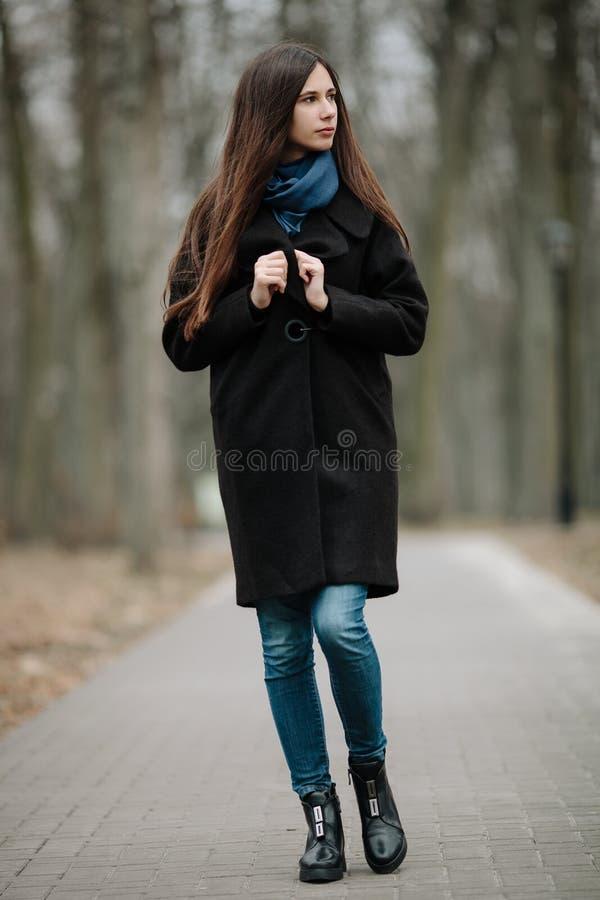 La jeune belle fille dans un manteau noir et l'écharpe bleue pour une promenade pendant l'automne/printemps se garent Une fille é image libre de droits