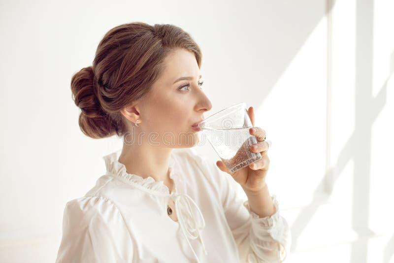 La jeune belle fille dans une chemise blanche se tient pr?s d'une fen?tre dans un bureau fonctionnant et de l'eau min?rale pure p photos libres de droits