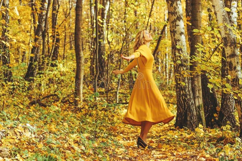 La jeune belle fille dans une longue robe jaune marche en parc d'automne avec les feuilles tombées images libres de droits