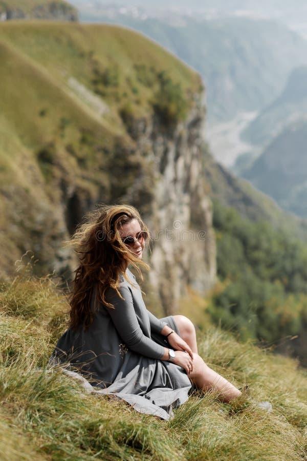 La jeune belle fille dans une longue robe s'assied sur une falaise à l'arrière-plan des montagnes photos stock
