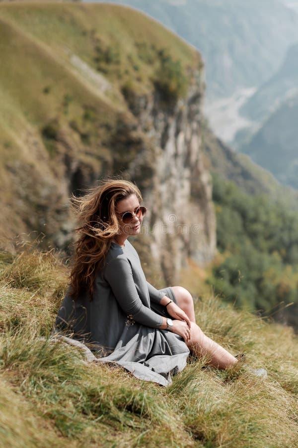 La jeune belle fille dans une longue robe s'assied sur une falaise à l'arrière-plan des montagnes photos libres de droits