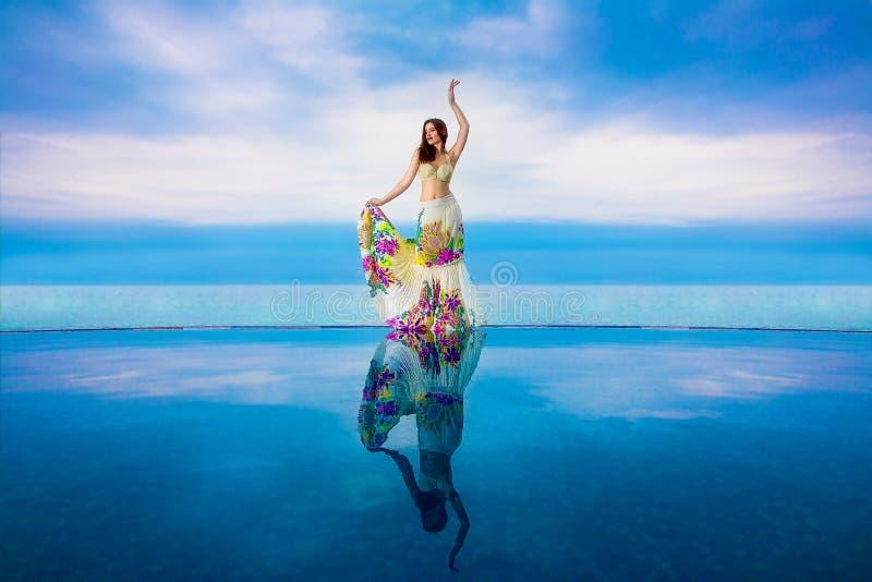 La jeune belle fille de brune dans un maillot de bain blanc avec une jupe de ondulation est à côté de la piscine d'infini Mer tro photographie stock