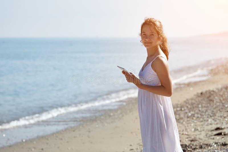 La jeune belle fille est souriante et regardante l'appareil-photo Fille dans la robe blanche sur la plage Tient un comprimé images libres de droits