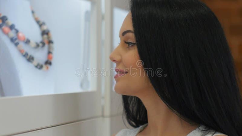 La jeune belle fille examine un étalage de bijoux dans le magasin image stock