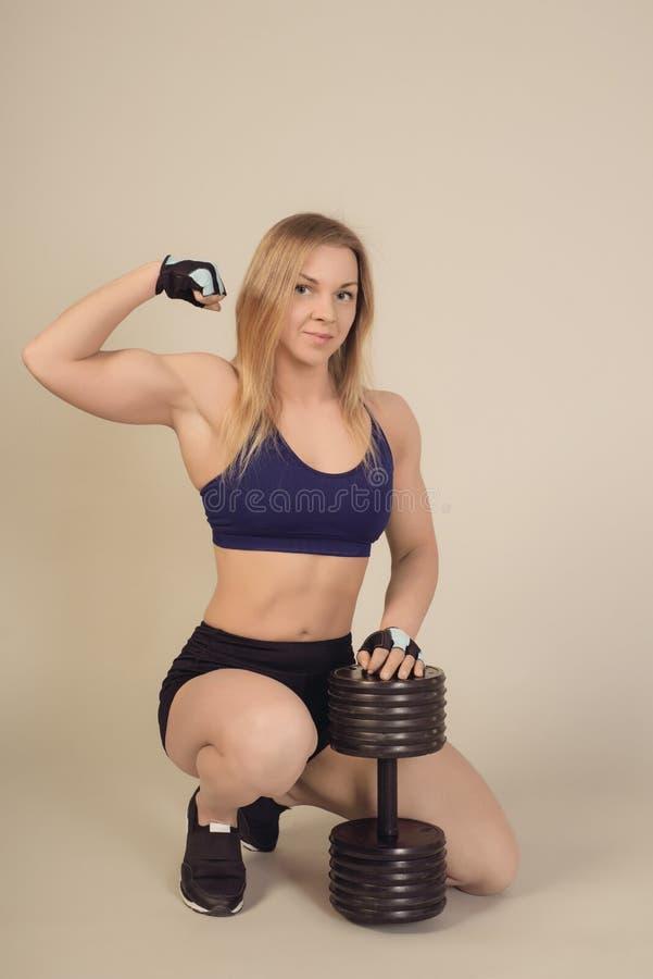 La jeune belle fille folâtre dans les vêtements de sport se reposant avec des haltères démontre le biceps photos stock