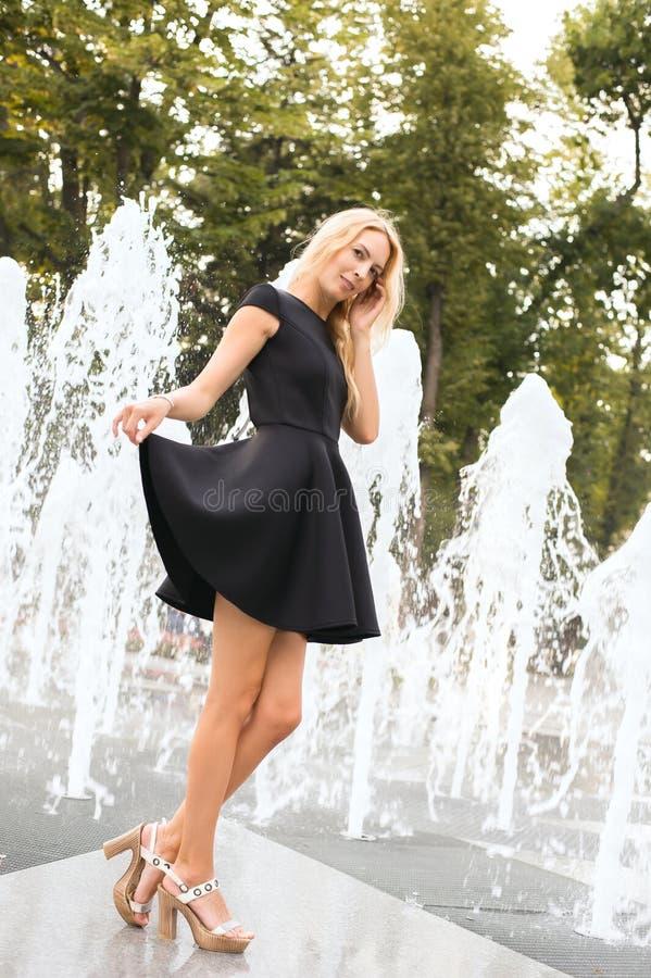 La jeune belle fille grande marche dans la robe à la mode noire dans la ville sur le fond des fontaines de la terre photographie stock libre de droits