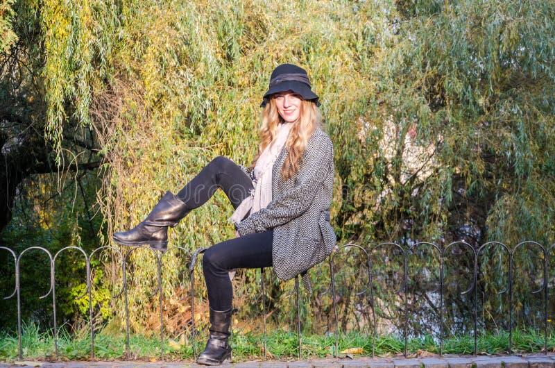 La jeune belle fille marche en parc d'automne parmi les feuilles jaunes dans un manteau un jour ensoleillé photos stock