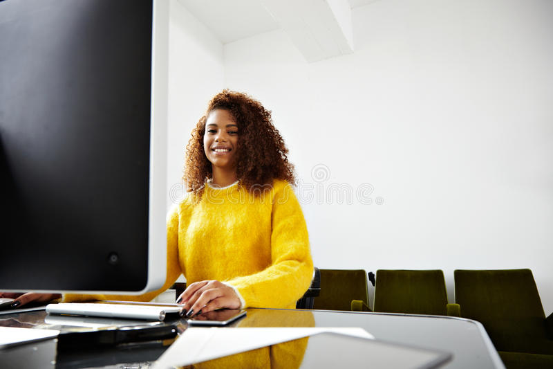 La jeune belle fille noire travaille dans le siège social photographie stock