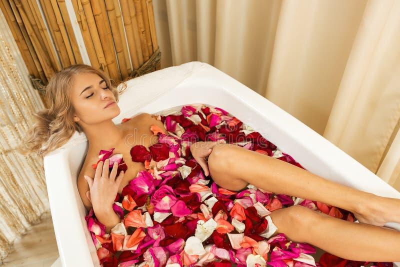 La jeune belle fille reçoit prendre le bain avec des pétales de rose dans la station thermale image libre de droits