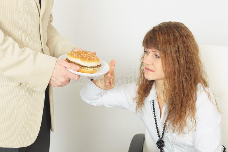 La jeune belle fille refuse la nourriture nuisible image stock
