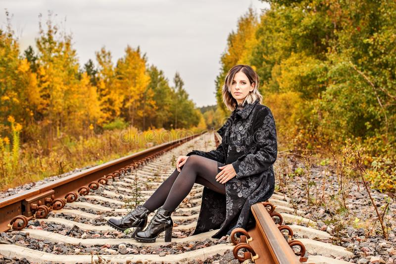 La jeune belle fille s'assied sur de vieux rails de forêt images libres de droits