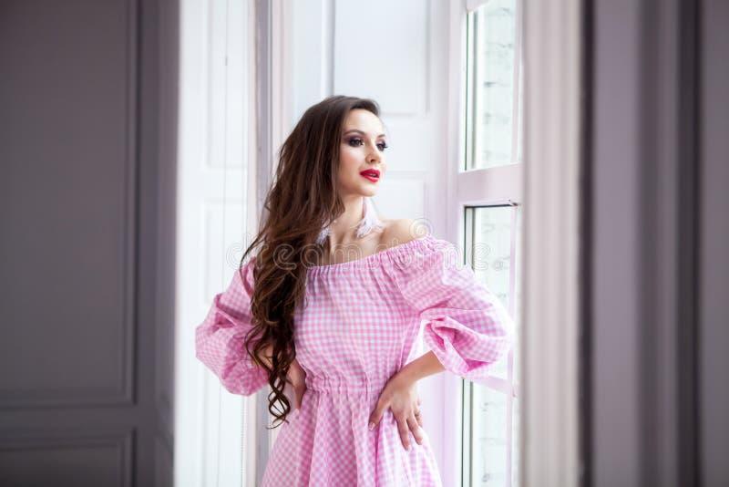 La jeune belle fille se tient à la grande fenêtre dans le plancher et examine la distance Habillé dans les dres roses à carreaux  image stock