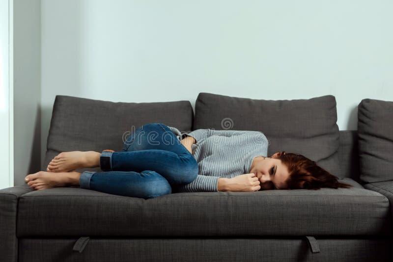La jeune, belle fille souffre des crampes d'estomac et de la douleur abdominale, se trouvant sur un sofa ? la maison Le concept d image stock