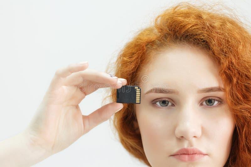 La jeune belle fille tient une commande d'instantané d'USB sur son temple image stock