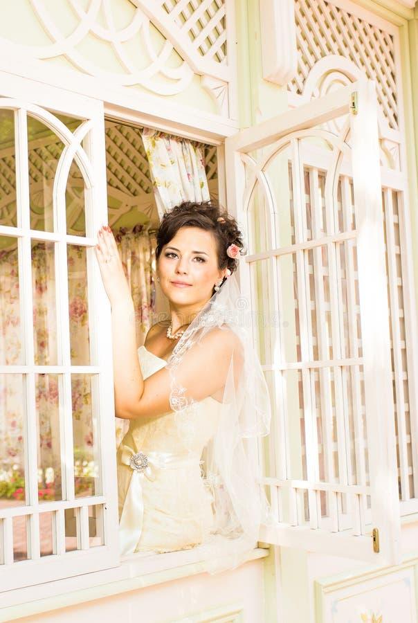 La jeune belle jeune mariée attend le marié près de la fenêtre Belle jeune mariée allumée par lumière du soleil belle jeune atten image stock