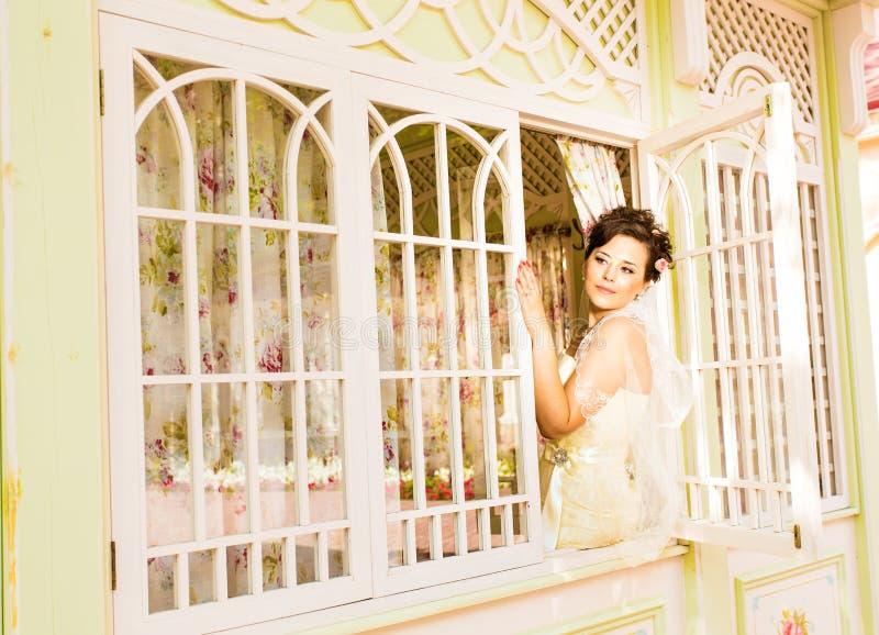 La jeune belle jeune mariée attend le marié près de la fenêtre Belle jeune mariée allumée par lumière du soleil belle jeune atten images libres de droits