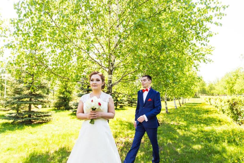 La jeune belle jeune mariée attend le parc de marié au printemps image stock