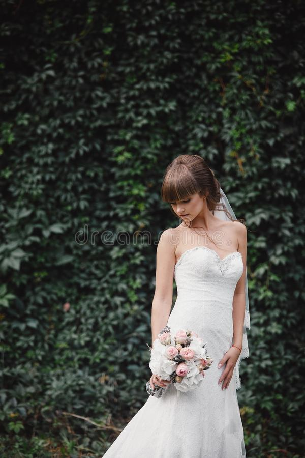La jeune belle jeune mariée dans une robe élégante se tient sur le champ près de la forêt et tient le bouquet photographie stock