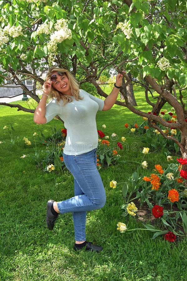 La jeune blonde avec un grand sein se tient en parc sous un arbre fleurissant images stock