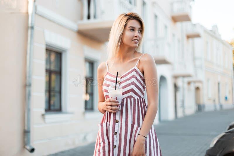 La jeune blonde gaie de femme dans une robe rayée rose à la mode avec un milkshake dans des ses mains détend la position sur la r photographie stock