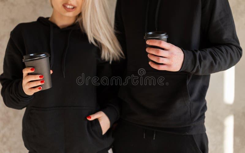 La jeune blonde heureuse de femmes avec un jeune homme élégant avec une barbe dans des vêtements noirs à la mode se tiennent près image stock