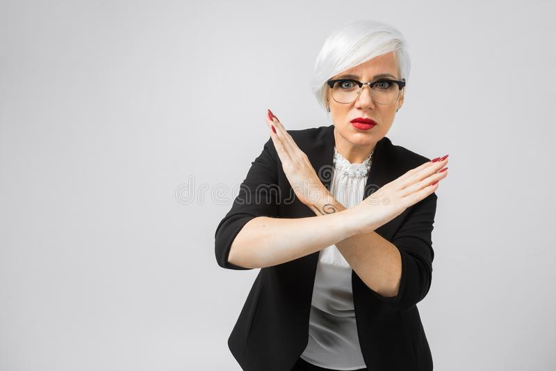 La jeune blonde juge deux bras croisés d'isolement sur le fond blanc image libre de droits