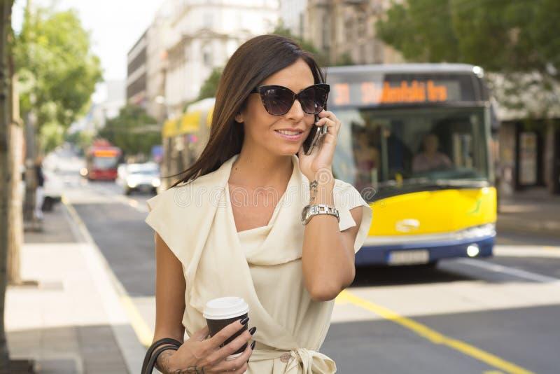 La jeune brune à la mode rit dans le téléphone photos stock